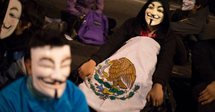 """MÉXICO, D.F., 05NOVIEMBRE2013.- Personas convocados por la """"Marcha del Millón de Máscaras"""" la que fue convocada alrededor del mundo el grupo de ciberactivistas conocidos como Anonymous, marcharon del Monumento a la Revolución y pretendían llegar al Zócalo capitalino, pero a la altura de el SAT en la avenida Hidalgo fueron encapsulado por alrededor de 500 granaderos. Los elementos de la policía capitalina impidieron el libre tránsito ha por lo menos 50 manifestantes durante una hora quienes marchaban de manera pacifica y en silencio. Al rededor del mundo participaron más de 400 localidades como parte de la manifestación coordinada. Cabe decir que en el encapsulamiento fueron retenidos también fotógrafos de medios de comunicación a quienes tambien se les impudio la salida. FOTO: ADOLFO VLADIMIR /CUARTOSCURO.COM"""